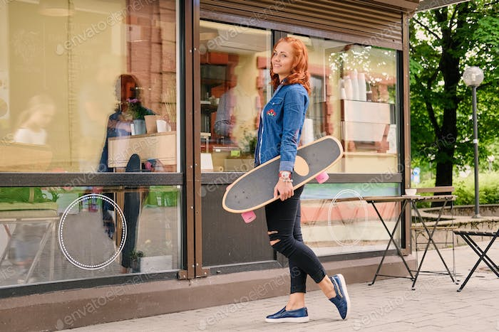 Attractive redhead female holds Longboard.