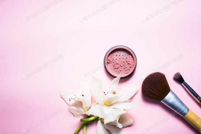 Puder, Pinsel und Blume auf rosa Hintergrund
