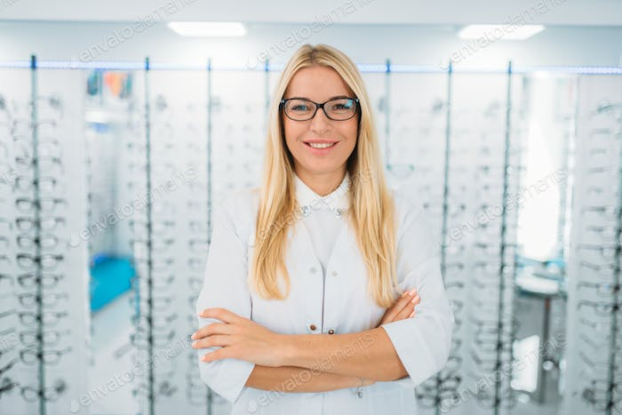Female optometrist against showcase with glasses