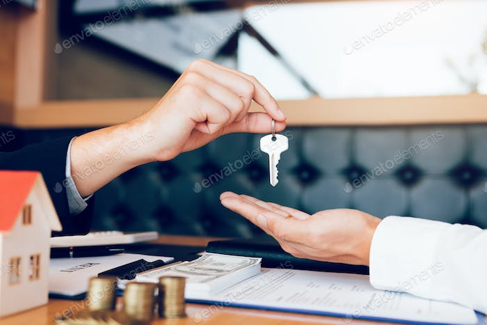 Close up of hand real estate agent passes the key to new homeowners in office.