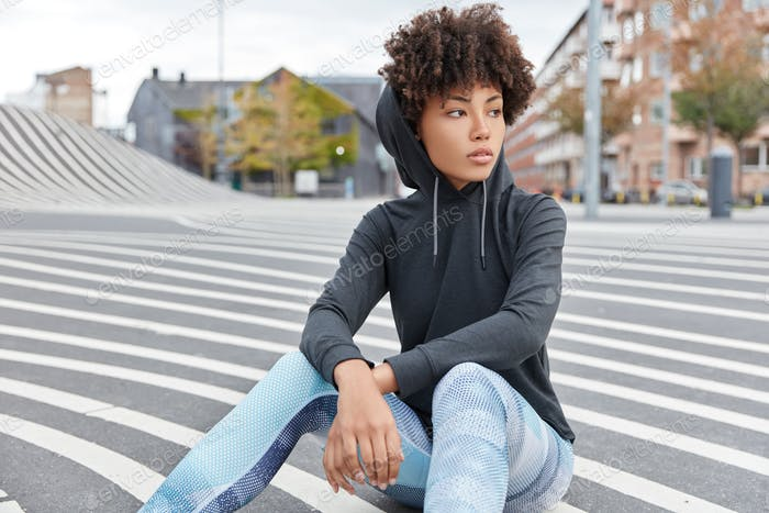 Carefree ethnic young woman wears casual sweatshirt with hood, leggings sits on road against urban b