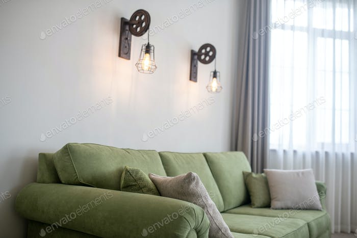 Wall-mounted lighting fixtures and a cozy velvet couch