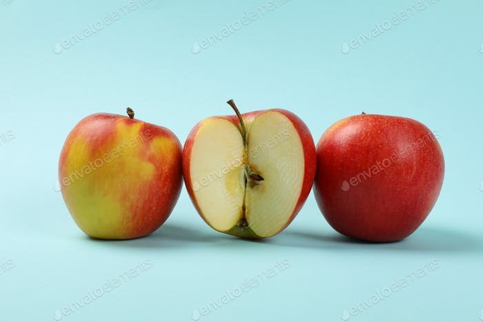 Ripe apples on blue background, close up