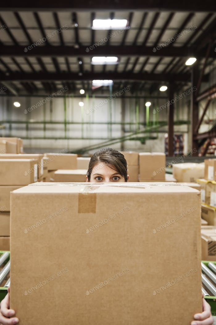 A caucasian female warehouse worker behind a cardboard box in a distribution warehouse.