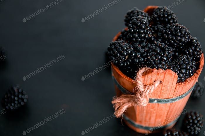 Black raspberries in a wooden basket on   background. Frame. Copy space. Top view.