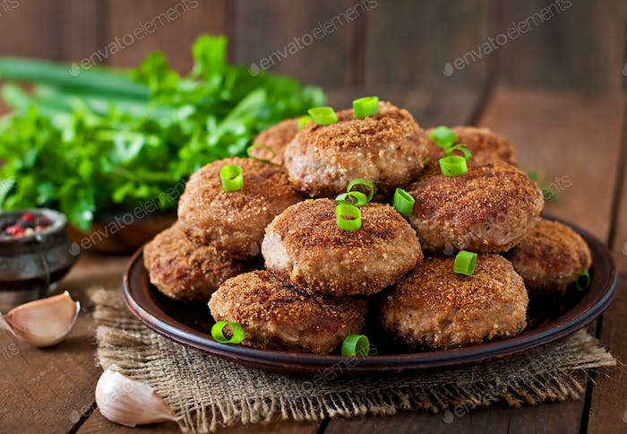 Juicy delicious meat cutlets on a wooden table in a rustic style.