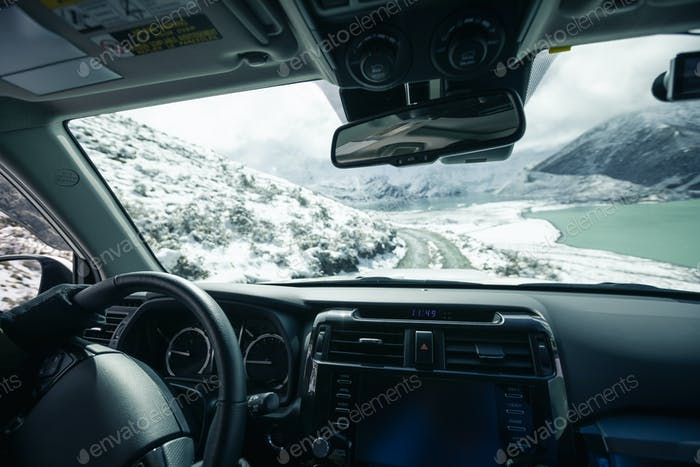 DrivingDriving off road car on snowing high altitude mountain trail on winter day