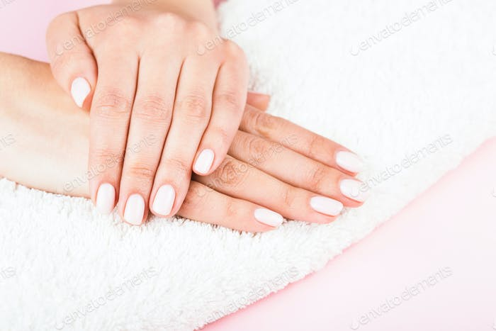 Female's Hands with Classic Pastel Manicure on White Towel.