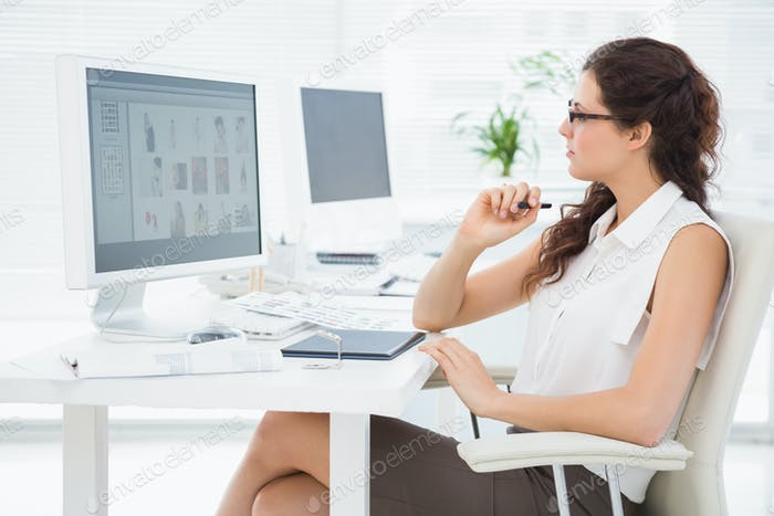Concentrated businesswoman using computer and digitizer in the office