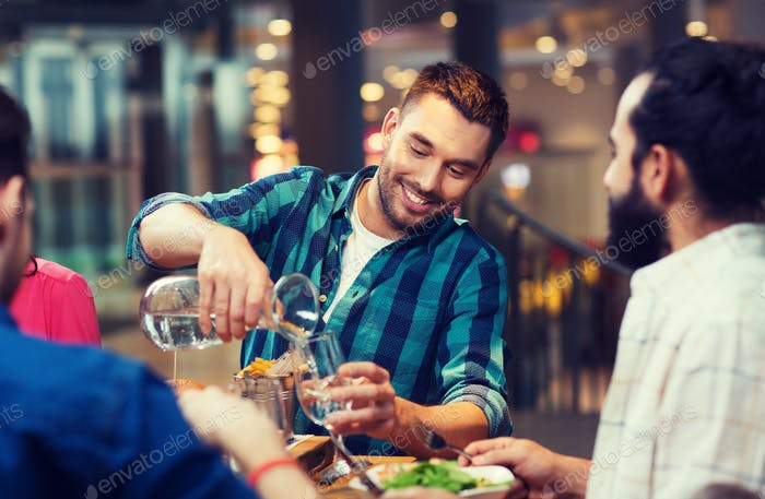 happy man with friends pouring water at restaurant