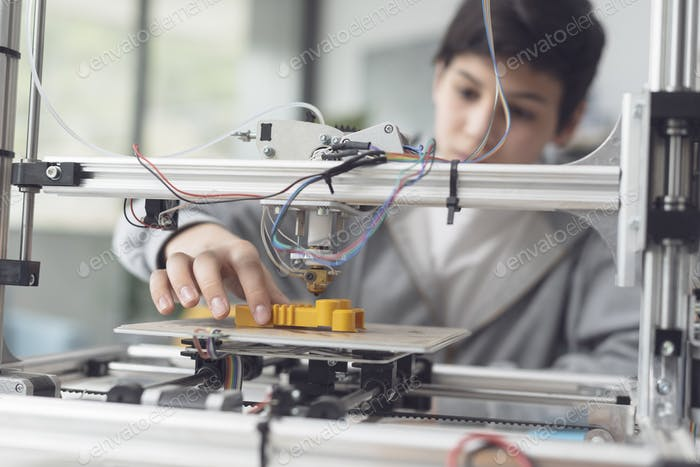 Boy printing a prototype using a 3D printer