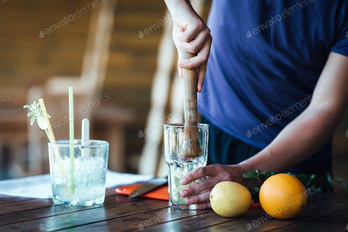 Barman prepares fruit alcohol cocktail based on lime, mint, orange, soda