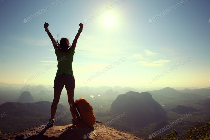 Successful hiker outstretched arms on sunrise mountain top