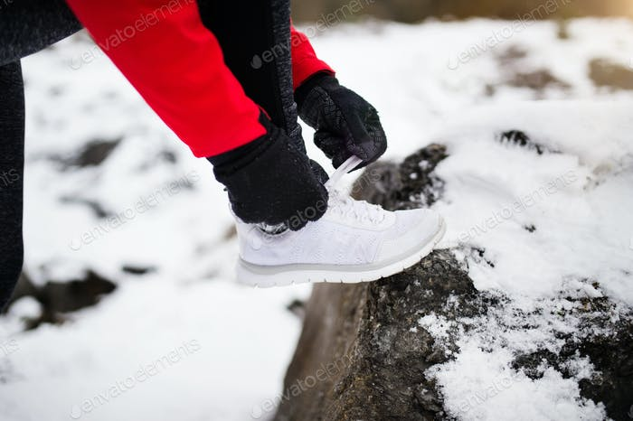 Unrecognizable woman jogging in winter nature.