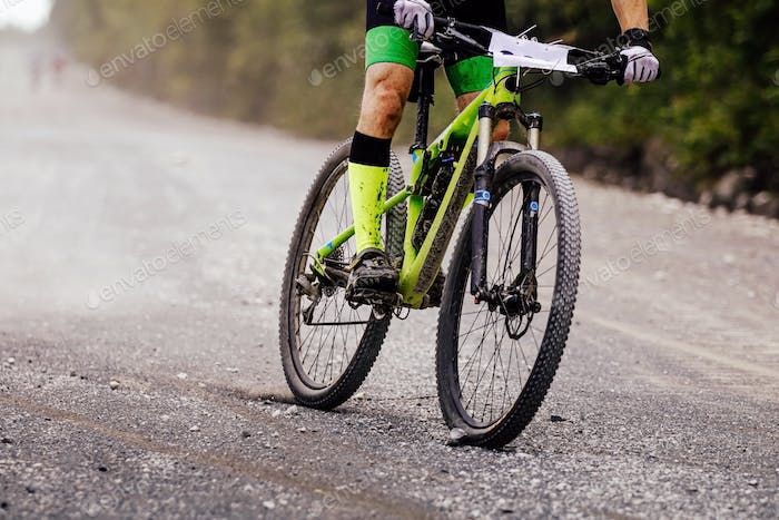 cyclist rider on mountain bike downhill on gravel road