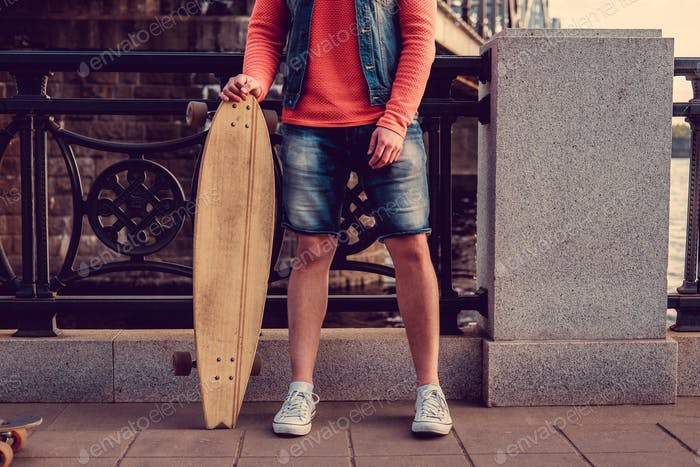 Man in jeans shorts holding longboard.