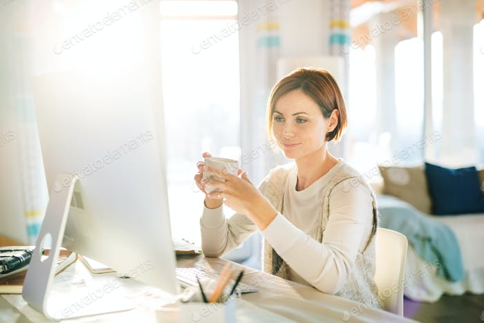 A young woman with computer and smartphone indoors, working in a home office.