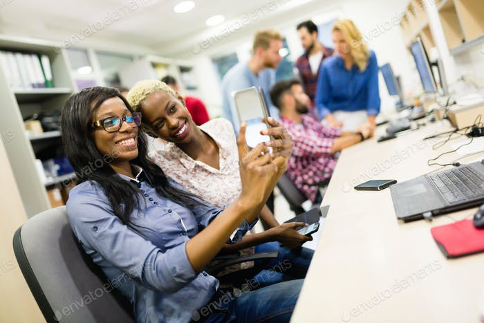 Happy colleagues taking selfies at office
