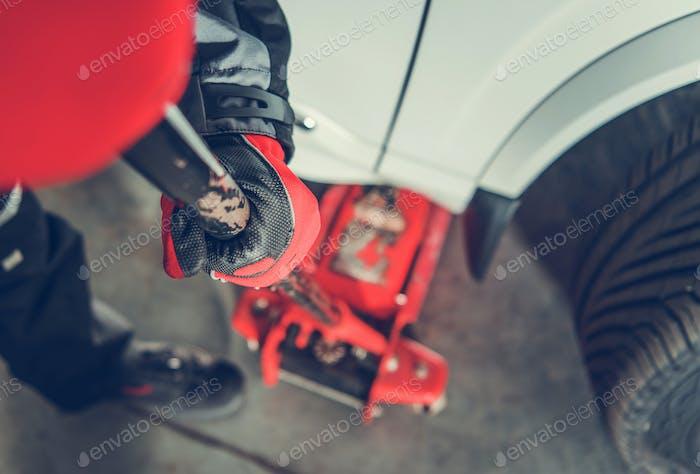 Car Mechanic Lifting Car Using Lift Jack