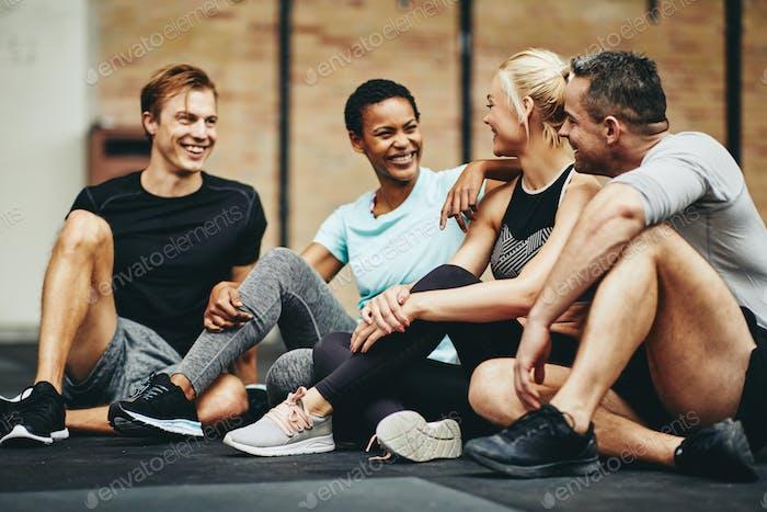 Lächelnde Freunde im Gespräch auf dem Boden eines Fitnessstudios