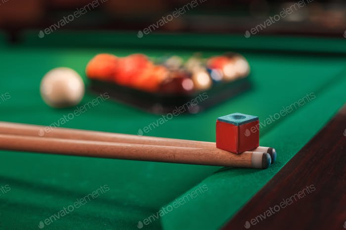 Cue and chalk on a pool table.