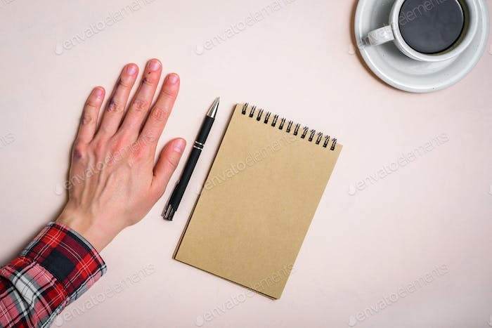 Left hand near note pad and coffee