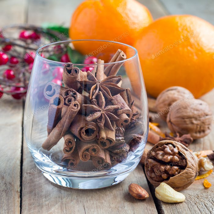 Cinnamon sticks and anise stars in glass with oranges and nuts on background, square