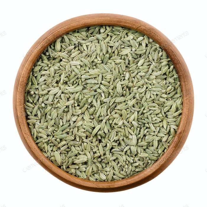 Fennel seeds in a wooden bowl over white