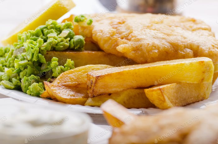 Traditional British street food fish and chips with mushy peas o