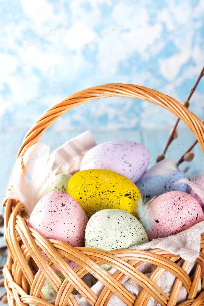 Colorful easter eggs in basket on blue wooden background. Close up