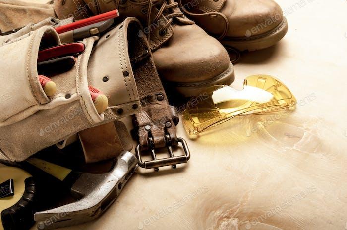 Konstruktionskonzept Hintergrund der Werkzeuggürtel gelbe Stiefel Schutzbrille Ameisenwerkzeuge auf Sperrholz