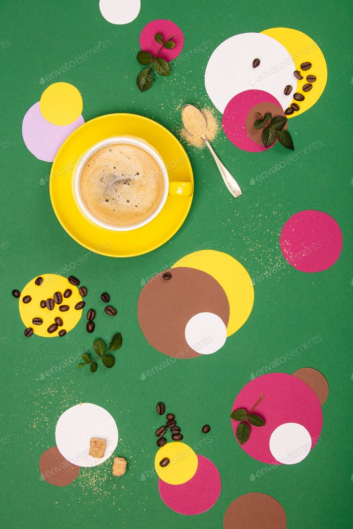 Cup of Coffee and colorful paper circles on green paper background