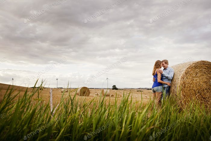 Side view of couple standing by hay bale on field against cloudy sky