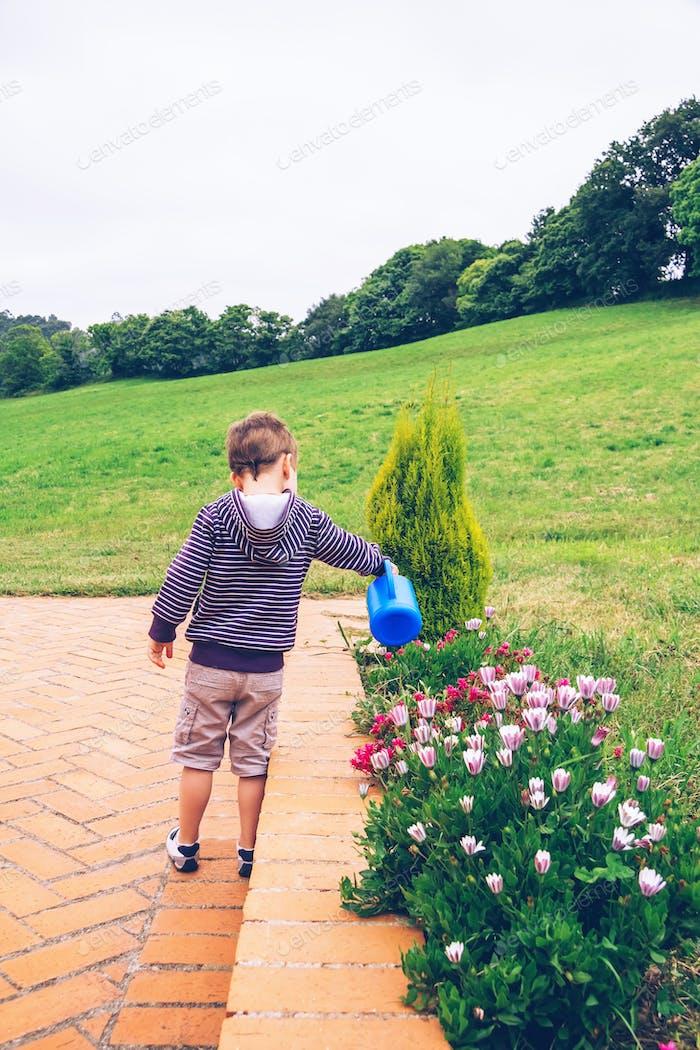 Happy boy watering flowers in the garden
