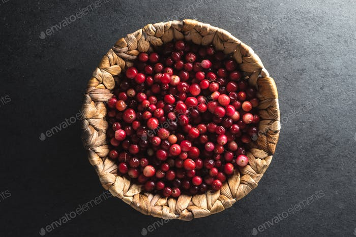Red cranberries in a basket on a gray stone