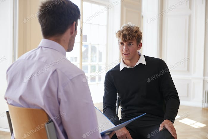Male Teenage Student Having Discussion With Tutor