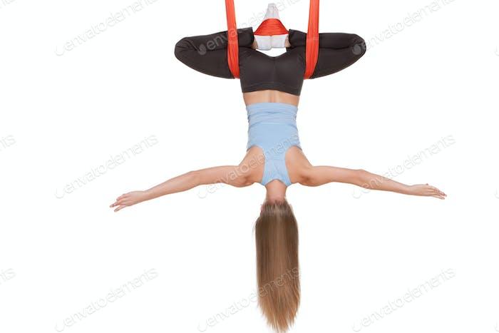 Junge Frau tun Anti-Schwerkraft Luft Yoga in Hängematte auf einem nahtlosen weißen Hintergrund.