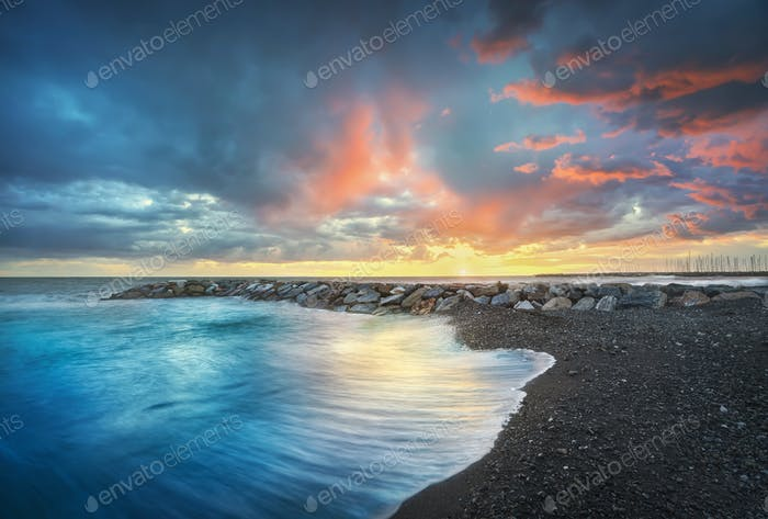 Stormy sea waves and foam at sunset. Marina di Cecina beach, Tuscany, Italy.