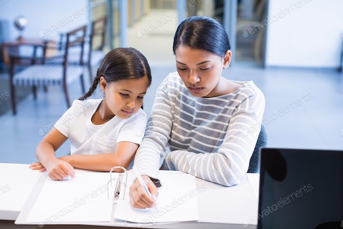 Mother and daughter filling out paperwork at counter