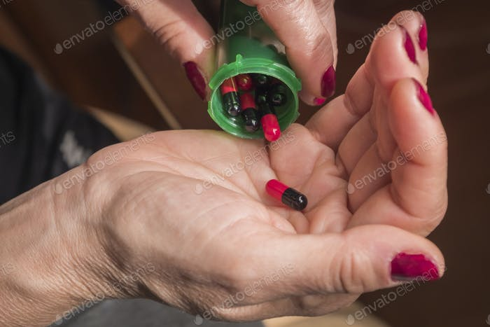 Women take red and black capsule with right hand from a green bottle on black background
