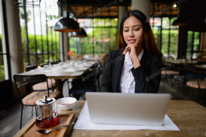 Happy young Asian businesswoman thinking while using laptop