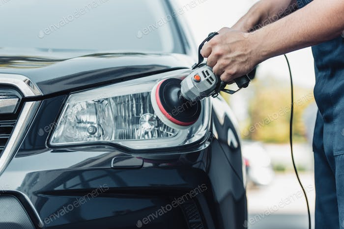 cropped view of car cleaner polishing headlamp with polish machine