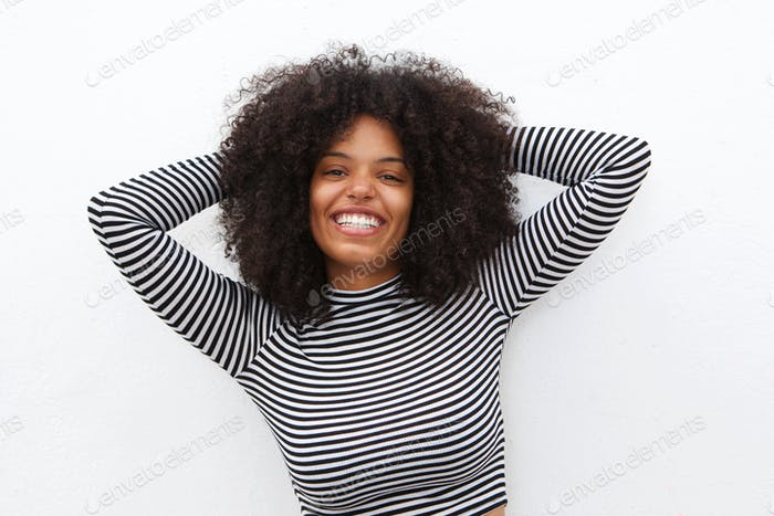 cheerful african american woman with hands in curly hair