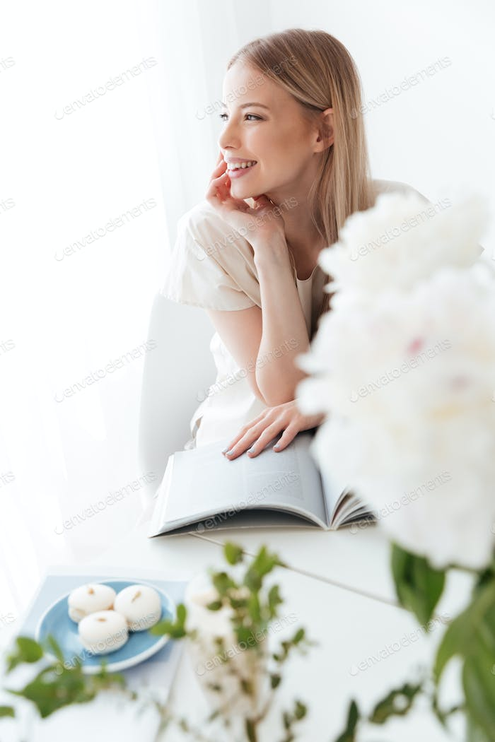 Happy woman sitting indoors reading book