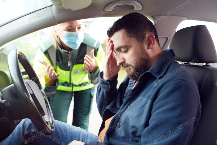 Female Paramedic Helping Male Driver With Whiplash Neck Injury Involved In Road Traffic Accident