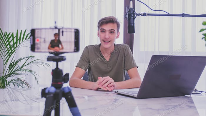 Teenage boy recording his video blog.