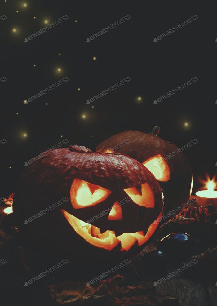 Two Halloween pumpkin Jack-o-Lantern on dark wooden background with fallen leaves and flames