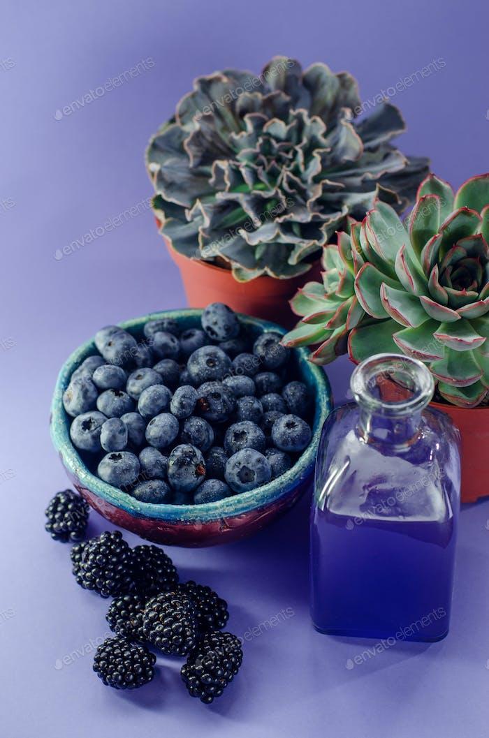 Черника в тарелке и ежевика и малины на синем фоне. Летний урожай.
