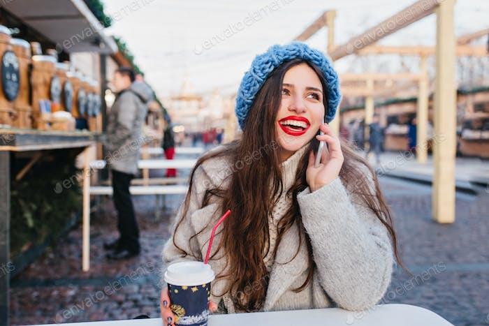 Outdoor portrait of excited brunette girl in woolen coat enjoying winter weekend in warm day. Photo
