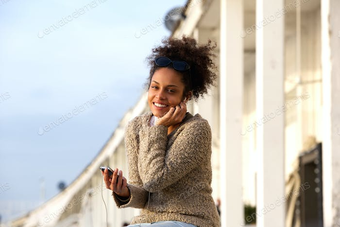 Woman listening on headphones from mobile phone